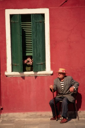 An elderly resident of Burano sits in the sun outside his home, dressed nattily in a straw hat and jacket.