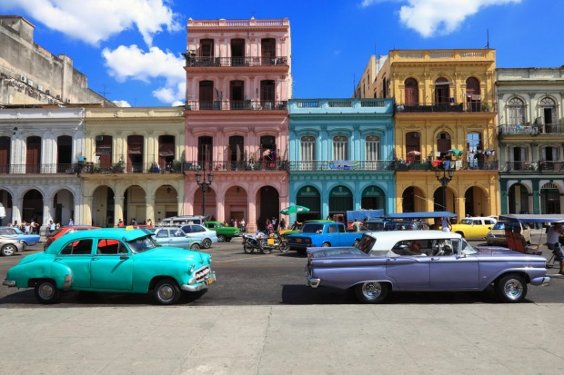 Vintage cars moving on the streets of colourful Havana, Cuba.