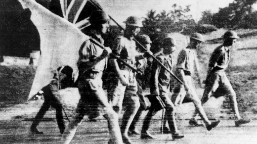 A surrender party from the British forces is escorted by a Japanese soldier in Singapore. They carry the white flag as ...