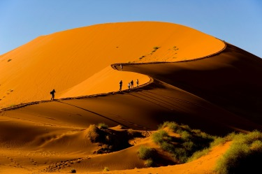 Tourists climbing Sossusvlei dune, Naukluft National Park, Namibia.