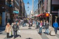 Shoppers and tourists strolling through the spring sunshine on the pedestrianised shopping street of Drottninggaten in ...