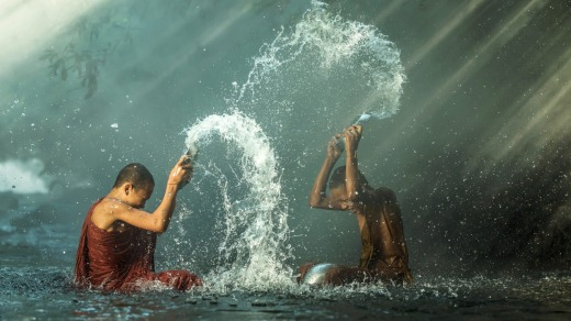 Young Buddhist monks splash each other during Songkran.