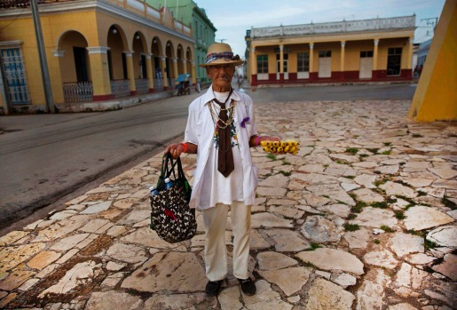 In this Sept. 1, 2016 photo, 90-year-old street vendor Antonio Bauza waits for tourists to sell his bananas, next to the ...