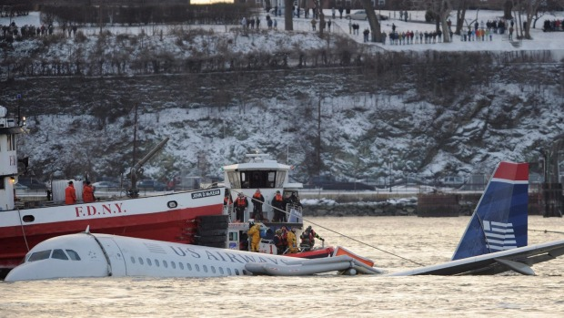Onlookers line the hillside as rescue workers surround the plane, slowly sinking into the Hudson River.
