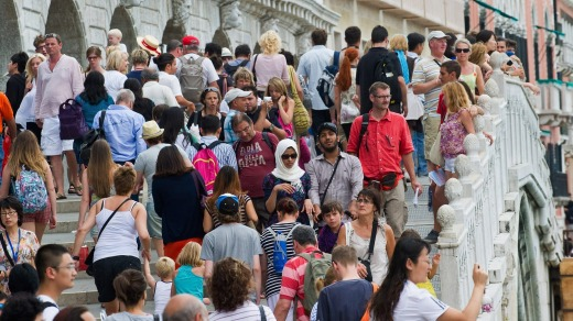 Tourists crowd on one of the bridges along Molo San Marco in Venice, Italy.