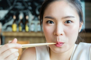 Woman eating with chopsticks inside japanese restaurant