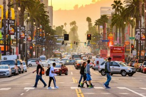 Pedestrians cross traffic on Hollywood Boulevard at dusk, Los Angeles.