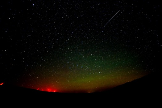The Northern lights can be seen in the horizon during the Perseid Meteor Shower on August 12, 2016 by the wind mills ...