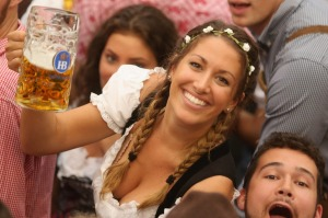 MUNICH, GERMANY - SEPTEMBER 17: Visitors hold up one-litre glasses of beer to kick off the 2016 Oktoberfest beer ...