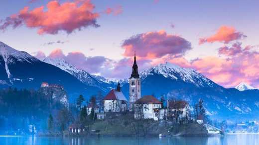 Sunset view of Julian Alps, Lake Bled with St. Marys Church of the Assumption on the small island.