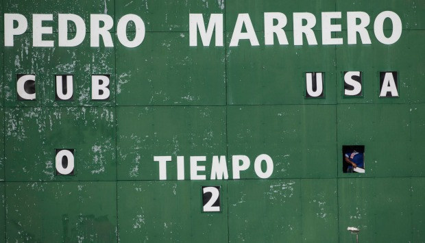 A stadium employee manually updates the scoreboards after the US scored its second goal against Cuba in their friendly ...