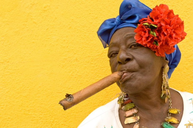 A Cuban woman, in traditional colonial costume, with a famous Cuban cigar in Old Havana.