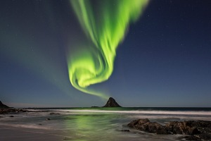 The green band of Auroras seem like smoke from the top of the rock.