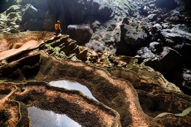 A cave explorer stands on rimstone formations in Hang Son Doong, Vietnam.
