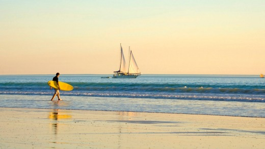 A surfer heads into the water at Cable Beach.