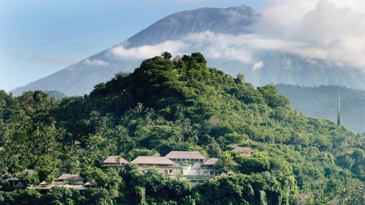 The resort of Amankila is carved into the hillside with cloud-swathed Mount Agung in the distance.
