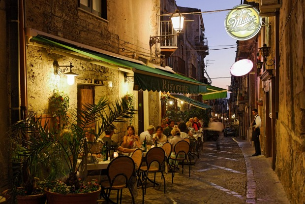 Guests sitting outside a restaurant in the evening, Cefalu, Sicily, Italy.