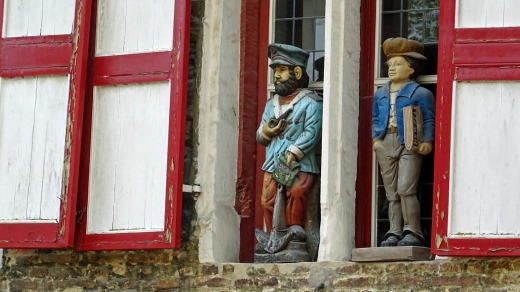 Carved wooden figures on a house in Bruges, Belgium.