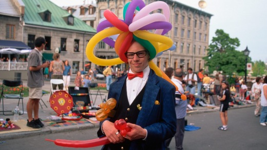 A man wears a balloon hat as he walks past the street vendors at Place Jacques Cartier in Montreal's Old Town.