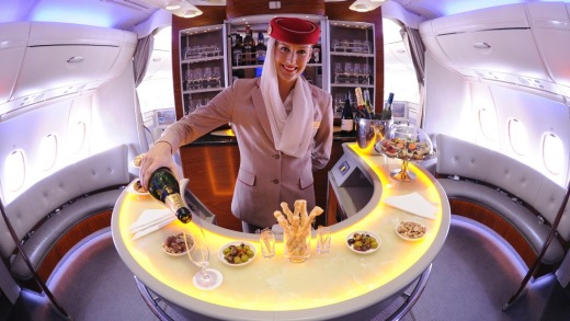Cabin crew serve champagne in the onboard lounge on an Emirates A380.