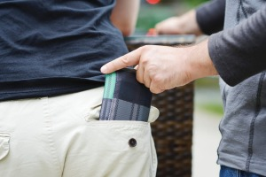 A pickpocket steals a wallet from a man's back pocket. str27cover-50 SCAMS Credit: iStock