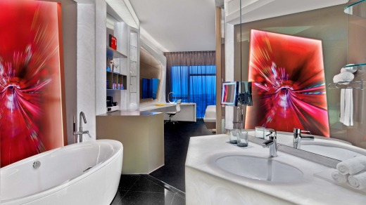The bathroom is open-plan highlighting the  luxurious bath.