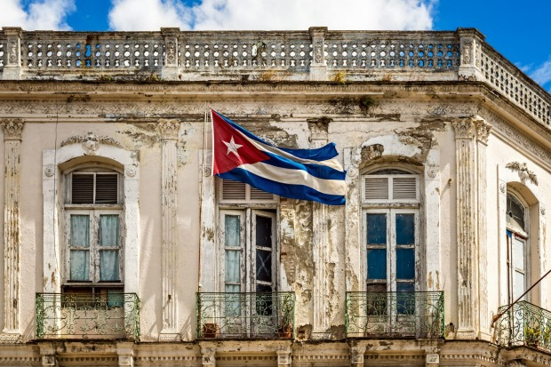 Cuban national flag on pole set on balcony of obsolete building in Santa Clara, Cuba.