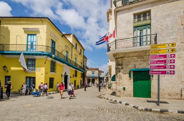 Tourists walk in the Plaza de la Catedral district with the Cuban and Canadian flags flying prominently from one of the ...
