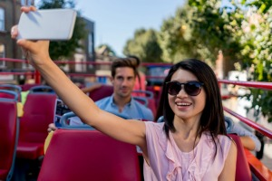 Portrait of a happy Asian woman taking a selfie on a tour bus in London - people traveling concepts. istock