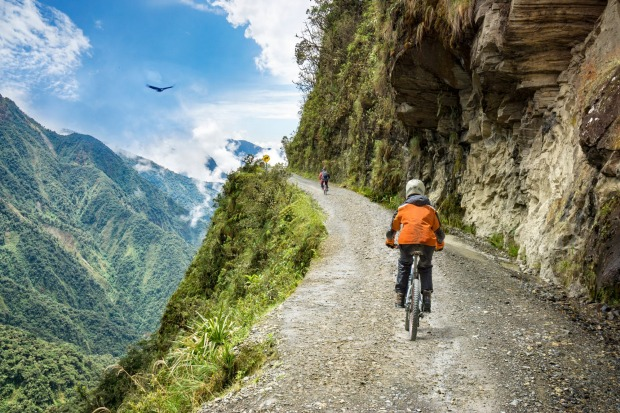 Bike tourists ride on Death Road in Bolivia.