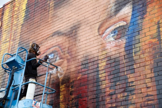 Adnate starts on his portrait of an Indigenous Australian man.