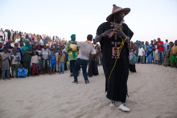 Musician playing a traditional flute at the music festival outside Timbuktu, Mali.