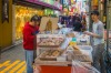 Man selling sweet pastries at a food stall in the Myeong-Dong shopping district under the colourful profusion of neon ...