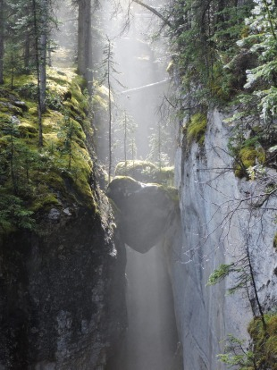The sunlight streaming through the mists to highlight suspended boulders in the Maligne Canyon, captured the spirit and ...
