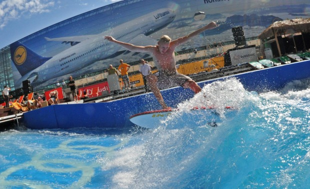 A man surfs on an artificial wave at an open area of the airport in Munich, Germany.