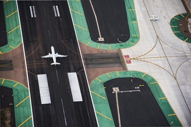 A passenger jet landing on the runway and a small private plane on a neighboring taxi-way at San Diego International Airport.