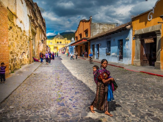 A woman and her child walk through the brightly coloured, but decaying stress of Antigua, Guatemala. This place is great ...