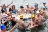 People celebrate with champagne glasses in the cold water of Lake Geneva, during the traditional New Year's swim in ...