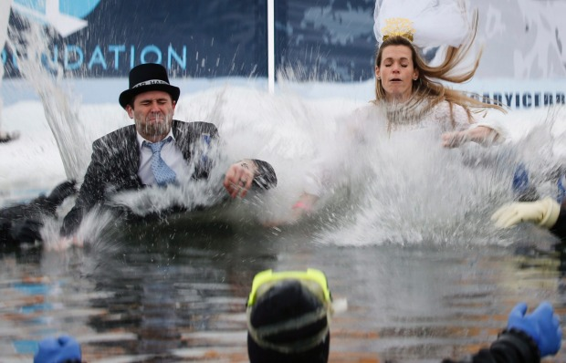 Kelsey Plett, left, and his wife Jill Plett celebrate their first wedding anniversary by leaping into a pond during the ...