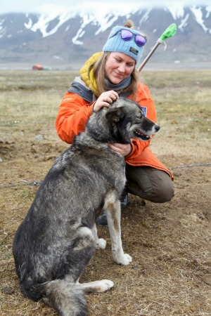 An armed guide enjoys a quiet moment with a husky.