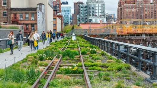 People walk along the High Line Park. The High Line is a popular linear park built on the elevated former New York ...
