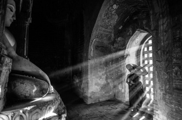 This young monk looking to Buddha in a temple in Myanmar (Burma) as the light streams through the window. Such a ...