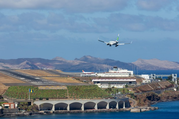 MADEIRA, PORTUGAL. The runway sits close to the sea at the base of a long sloping hill that generates powerful ...