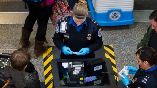 Transportation Security Administration (TSA) officers check passenger's identification at a security checkpoint at ...