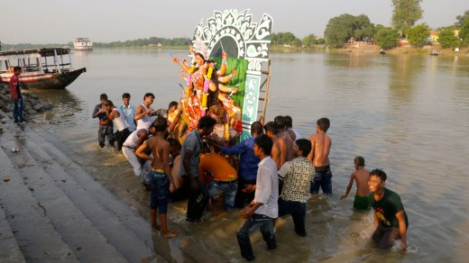 An effigy of Hindu goddess Durga is thrown into the Ganges at the end of a festival.