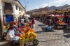 People selling and buying fruits at a market in the steets of Cusco, Peru.