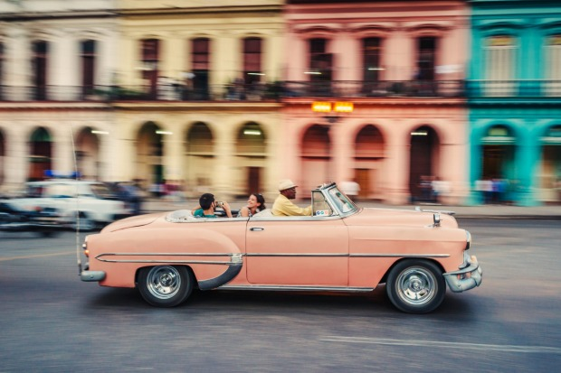 Tourists ride in a classic American car that serves as a taxi, in Havana, Cuba.
