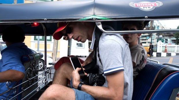 Two male passengers and a driver sit in a tuk-tuk in Bangkok, Thailand.