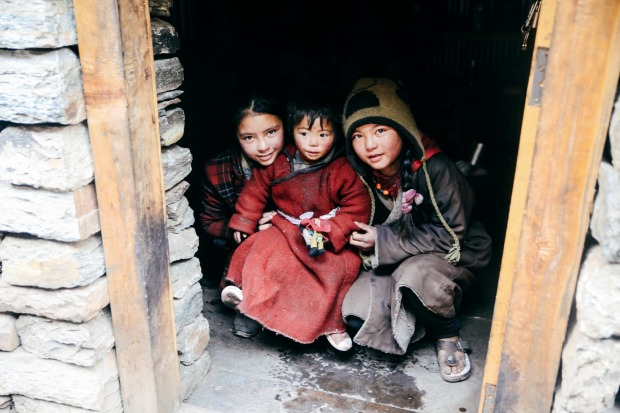 Inquisitive kids peering out of their doorway Nepal.