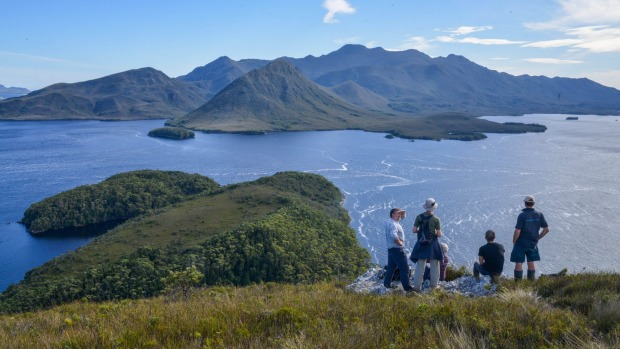 Guide Peter Marmion (L) with tourists from the Odalisque on top of Balmoral Hill, Port Davey.